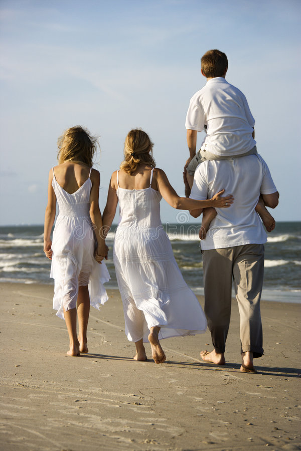 Family walking down beach. Caucasian family of four walking on beach with dad carrying son on shoulders