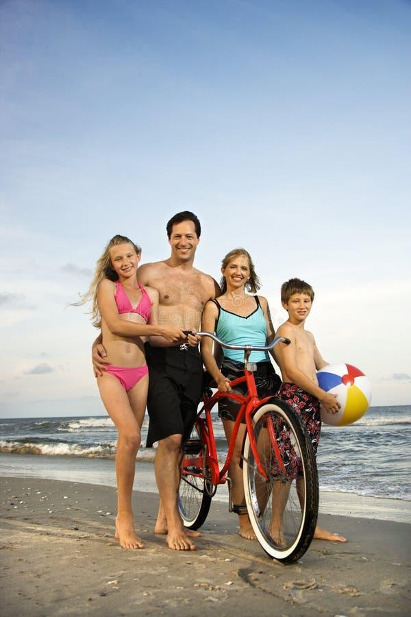 Family walking down the beach. Caucasian family of four walking on beach stock photos