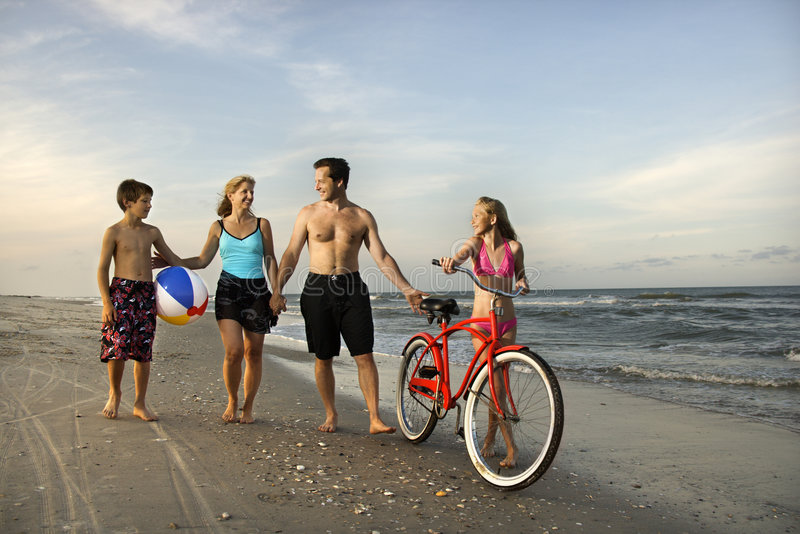 Family walking down the beach. stock images