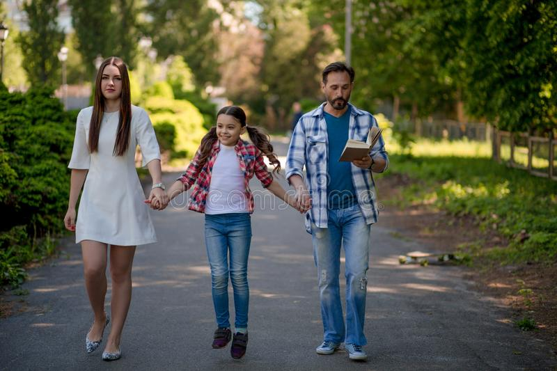 Family Walking Down The Road Outside In The City Park. Family Is Holding Each Other Hands. The Gaughter is Between stock photos