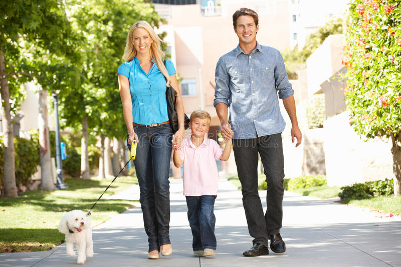 Family walking down the street with dog. Smiling at camera royalty free stock photos