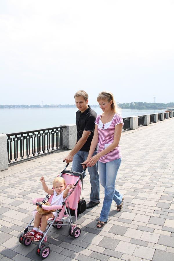 Family walking on embankment royalty free stock image