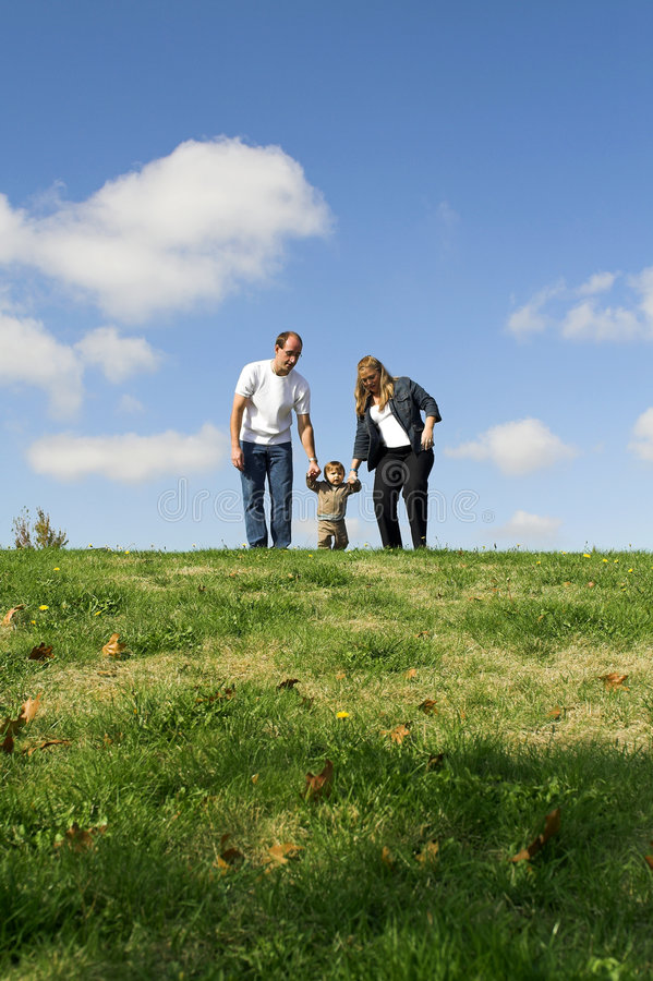 Family walking on field royalty free stock photo