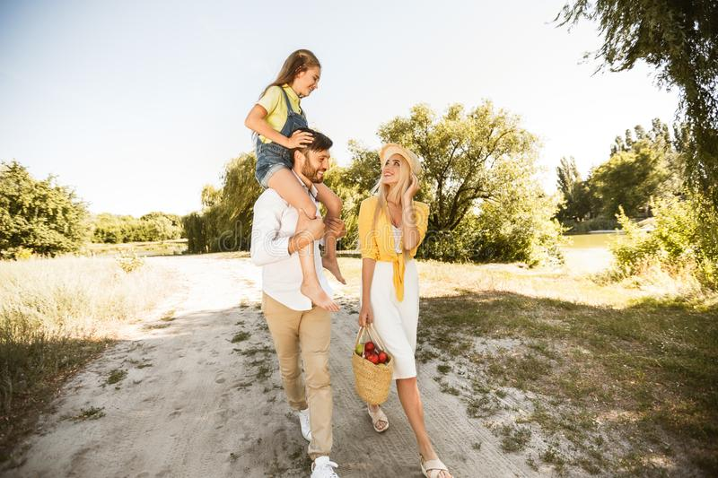 Family walking in nature, girl sitting on father`s shoulders royalty free stock images