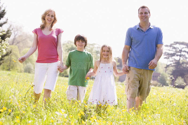Family walking outdoors holding flower smiling stock photography