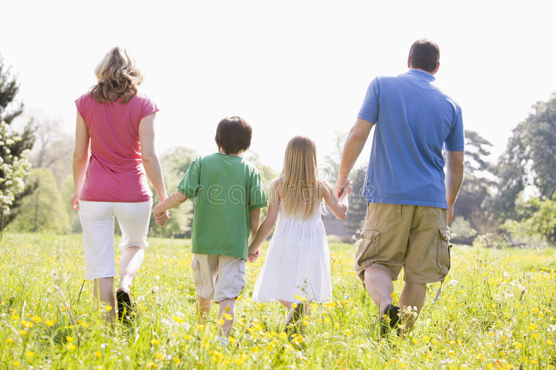 Family walking outdoors holding hands royalty free stock photo