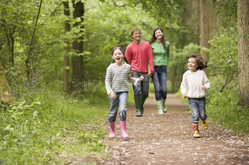 Family walking on path holding hands smiling royalty free stock photo