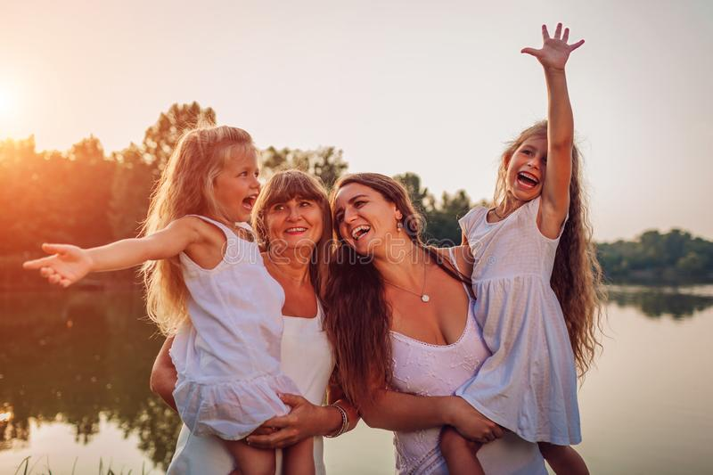 Family walking by summer river at sunset. Mother and grandmother holding kids and laughing. Three denerations royalty free stock image
