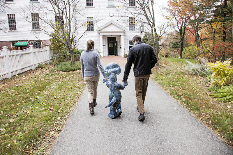 Family walking to school. Parents holding hands walking child wearing costume into school royalty free stock photo