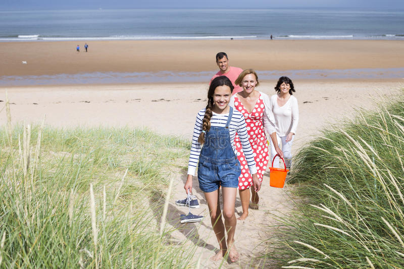 Family walking up sand dunes royalty free stock photo