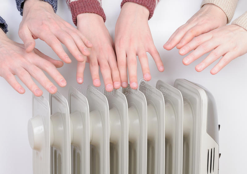Family warming up hands over electric heater royalty free stock images