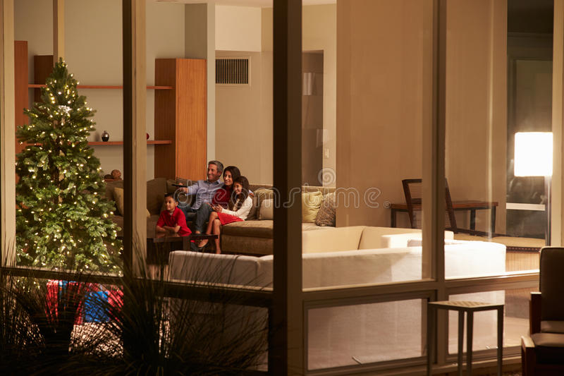 Family Watching Christmas TV At Home Viewed From O Stock Photos