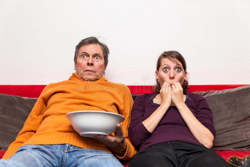 Family watching a creepy movie. Father and daughter on a couch watching a creepy movie stock photography