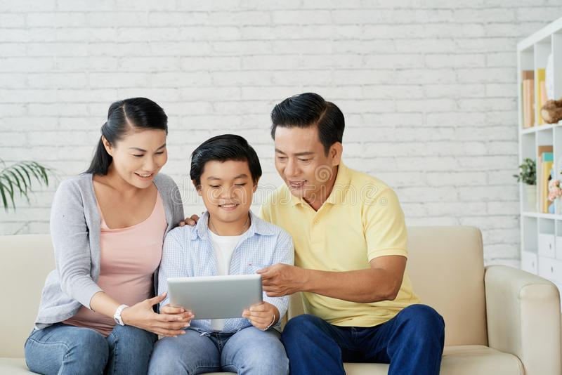 Family watching movie on digital tablet. Happy mature Vietnamese couple and their teenage son watching something on tablet computer royalty free stock photography