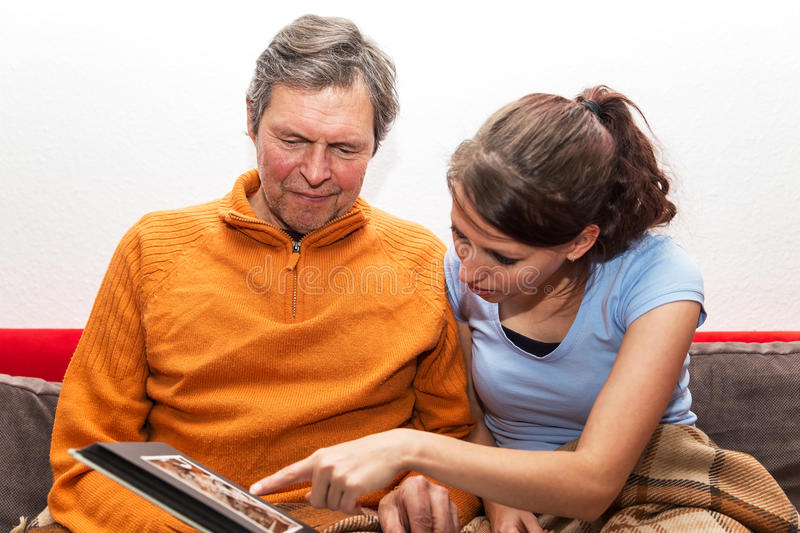Family are watching a photo album. Father and daughter are watching photos royalty free stock photography