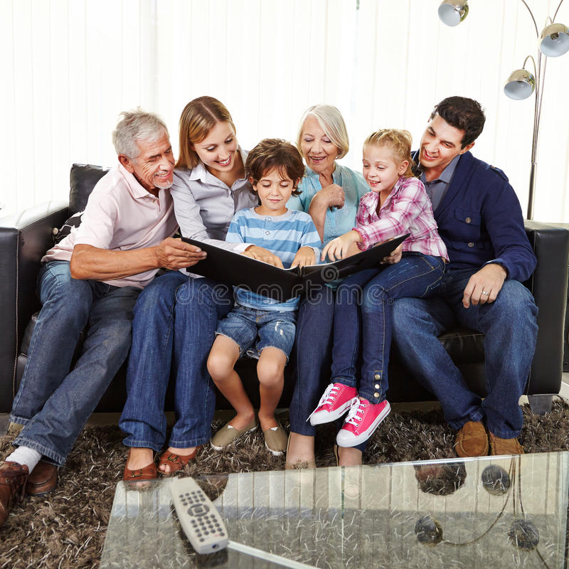 Family watching photo album in living room royalty free stock photos