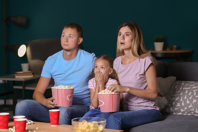 Family watching scary movie in evening royalty free stock photos