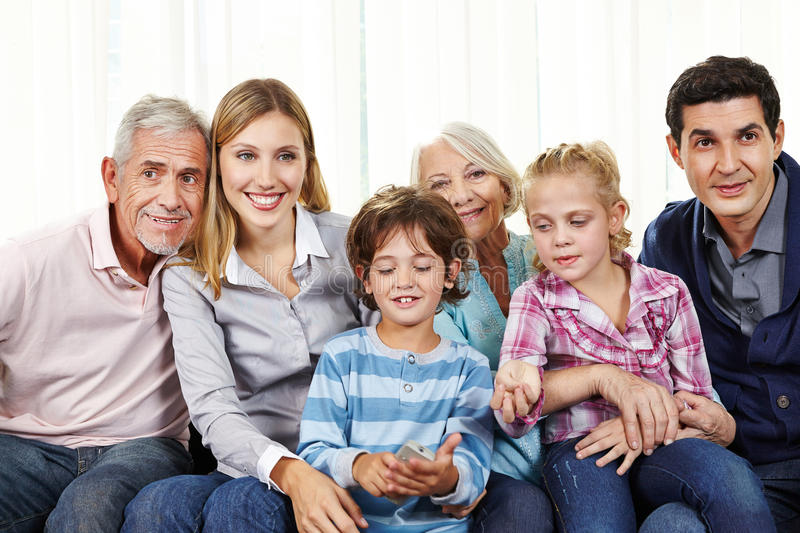 Family watching Smart TV in living room. Family watching Smart TV with remote control in living room royalty free stock photos
