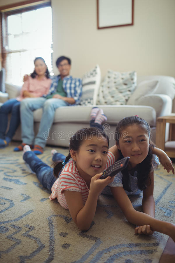 Family watching television together in living room stock image