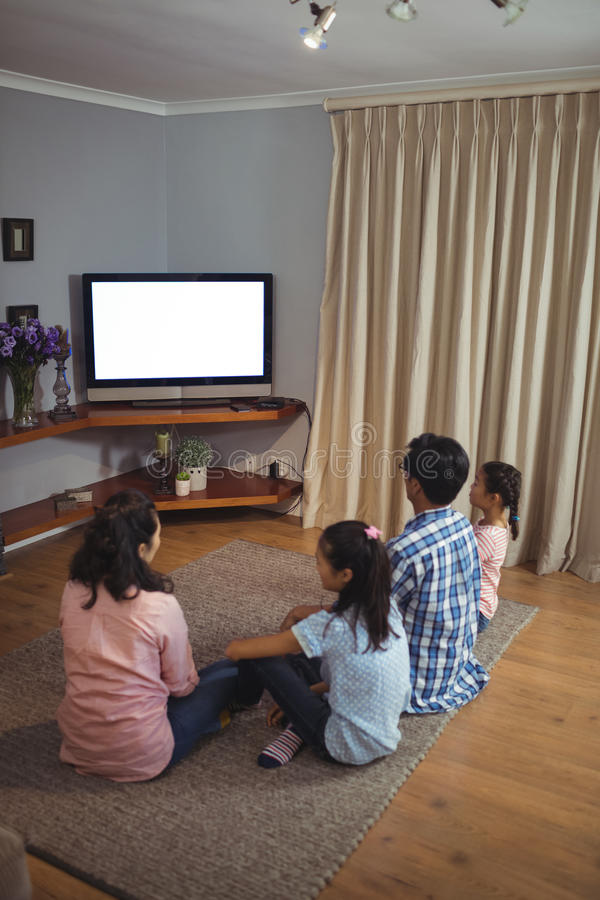 Family watching television together in living room stock images