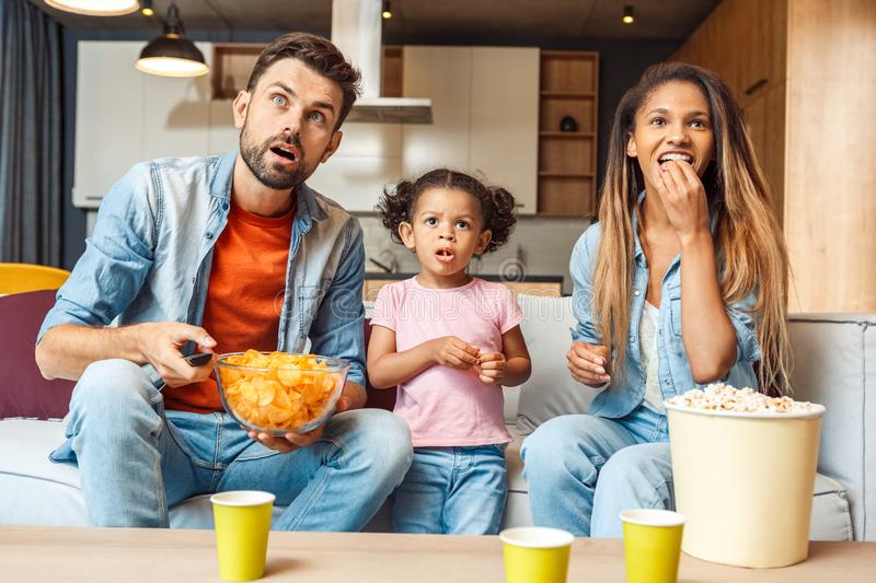 Family watching tv, eating chips and spending day together at home. Shocked young adult father and mother sitting on comfort couch with cute african child girl stock photo