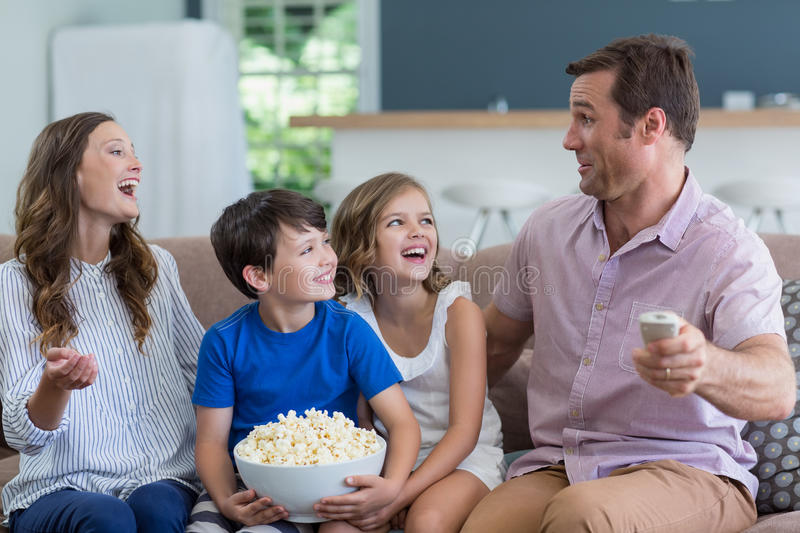 Family watching tv and eating popcorn in living room at home royalty free stock photo