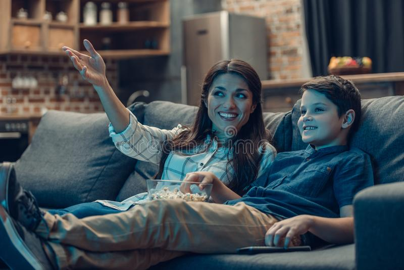 Little son and his young mother talking while watching tv on couch. And eating popcorn royalty free stock image
