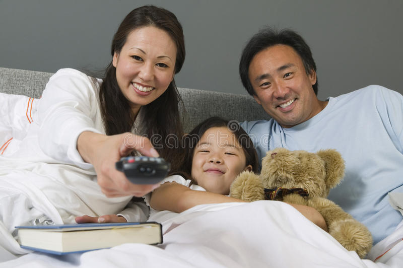 Family Watching TV Together In Bed stock image