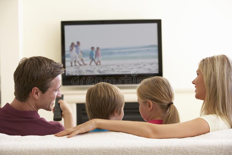 Family Watching Widescreen TV At Home stock photography