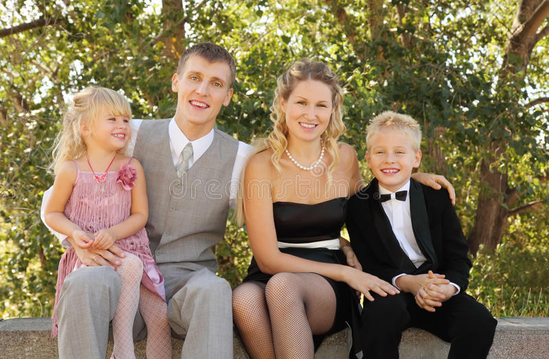 Family wearing holiday clothes sit and smile stock image