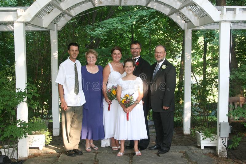 Family wedding portrait. A happy family of 6 poses for a wedding portrait together in a garden royalty free stock image