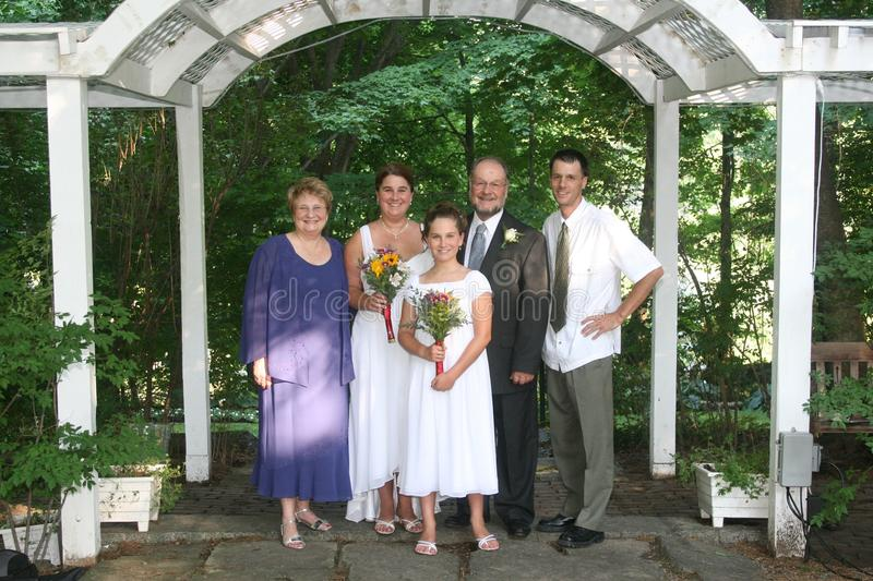 Family wedding portrait. A formal family wedding portrait under an outdoor archway or trellis stock images