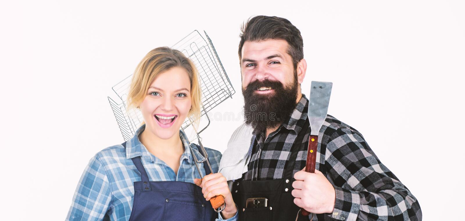 Family weekend. Couple in love hold kitchen utensils. Man bearded hipster and girl. Preparation. Tools for roasting meat royalty free stock photography