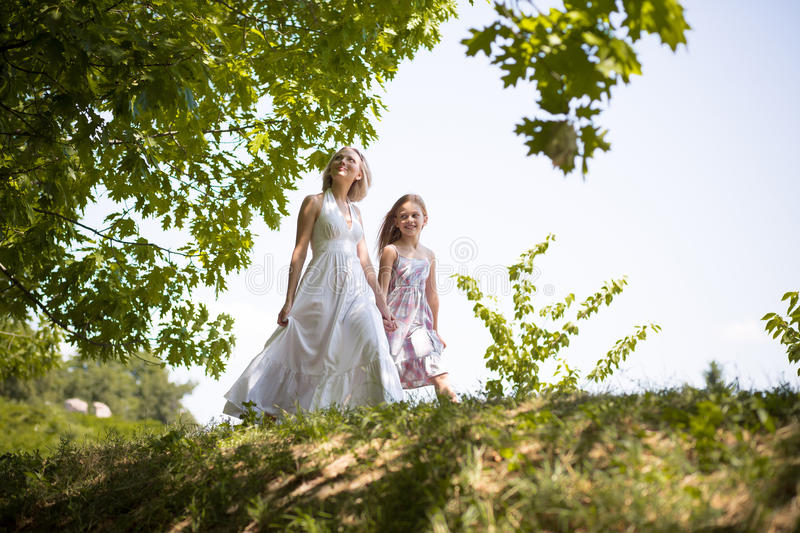 Family weekend mother and daughter walking, holding hands in forest. royalty free stock photography