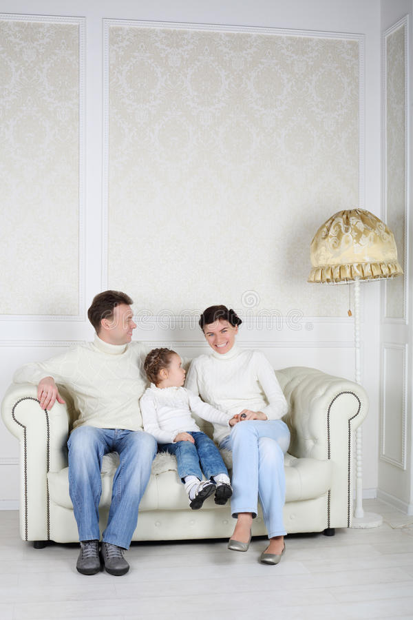 Family in white sweaters and jeans sit on sofa at home. Father and daughter look at smiling mother stock photos