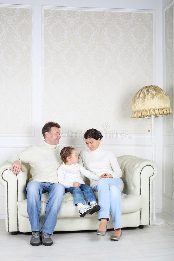 Family in white sweaters and jeans sit on white sofa. In white room at home. Father and daughter look at mother stock image