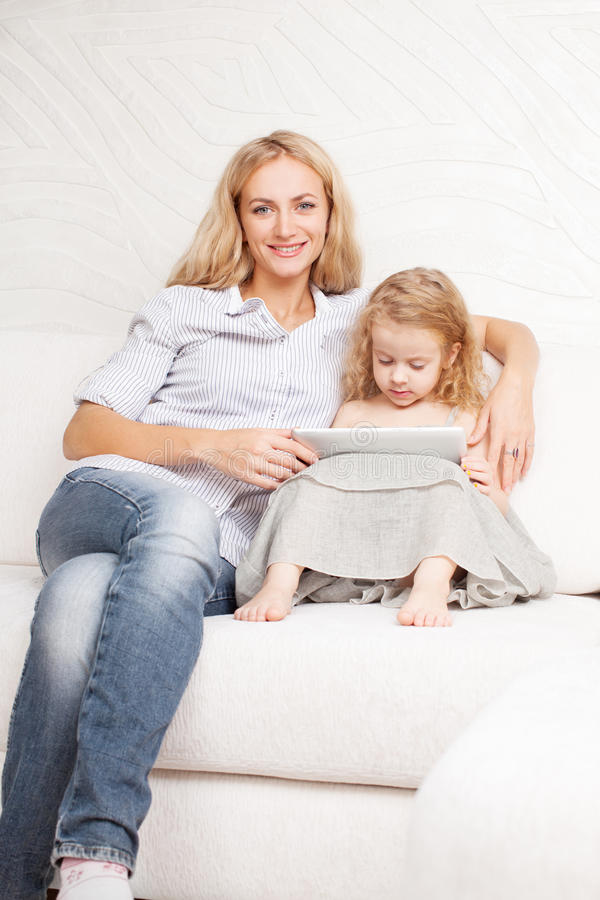 Family wiht tablet at sofa stock photos