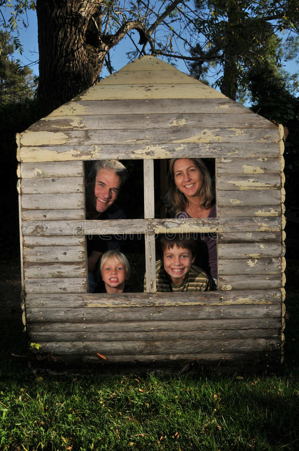 Family in the windows of a very small house stock images