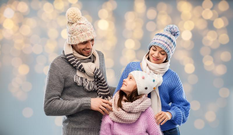 Family in winter clothes over christmas lights stock photos