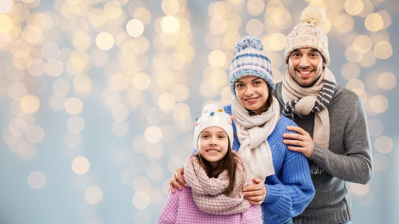 Family in winter clothes over christmas lights stock images