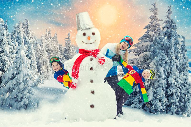 A family in a winter snowy forest mold a big snowman.Family winter fun for Christmas vacation. royalty free stock image