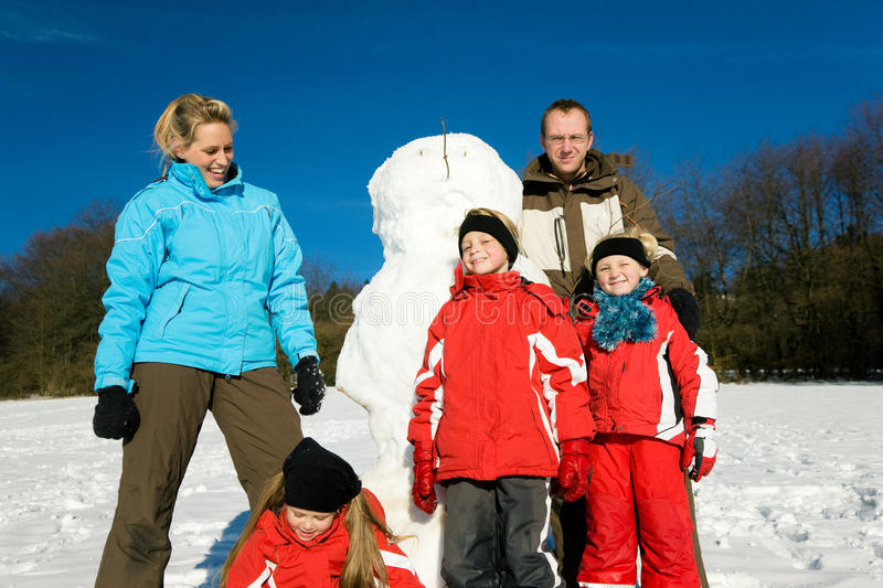 Download Family In Winter Standing In Front Of Their Snowma Stock Photo - Image: 12270398