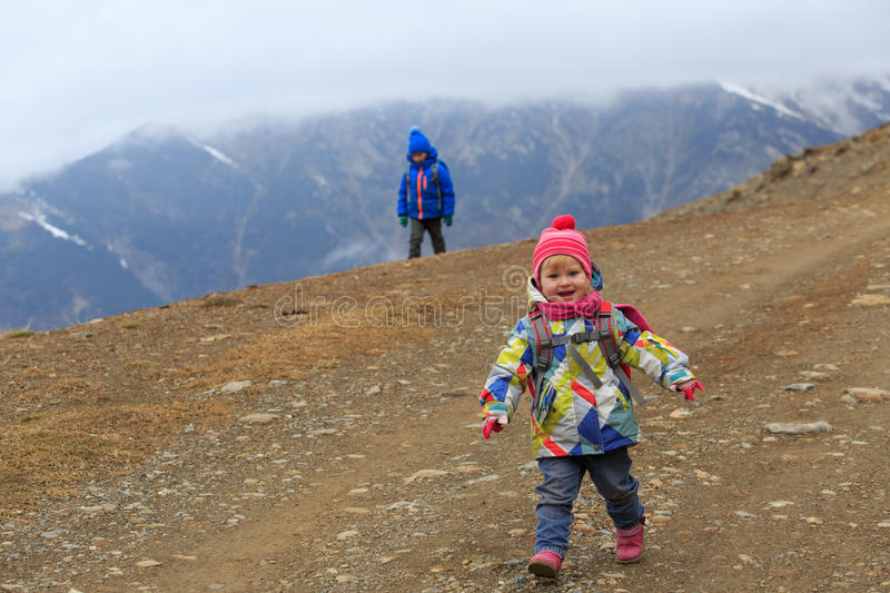 Family winter travel - little girl and boy hiking in mountains royalty free stock photo