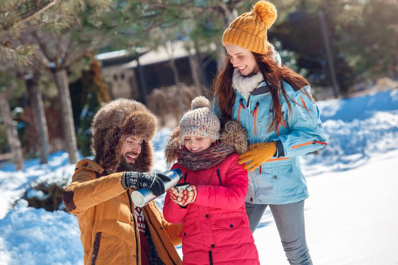 Winter vacation. Family time together outdoors standing man pouring hot tea into girl`s cup smiling joyful stock photography