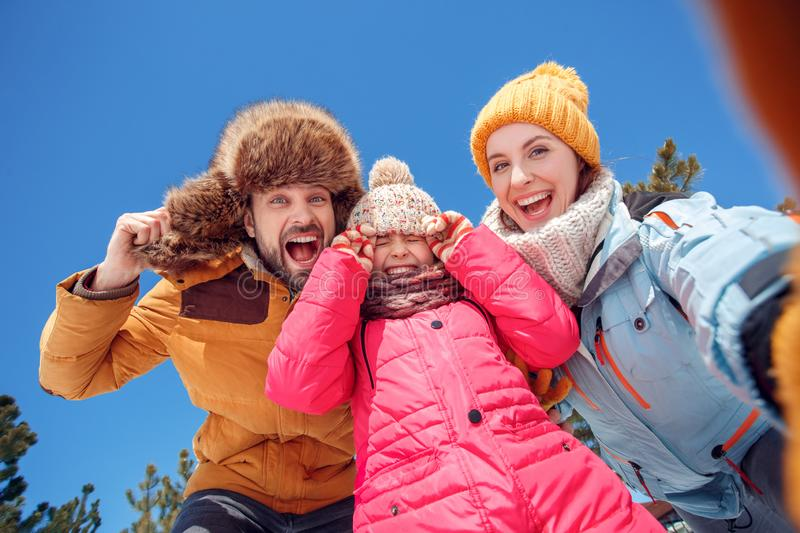 Winter vacation. Family time together outdoors taking selfie holding hats laughing excited bottom view close-up stock image