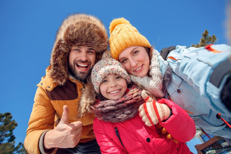 Winter vacation. Family time together outdoors taking selfie shhowing thumbs up smiling toothy bottom view stock photo
