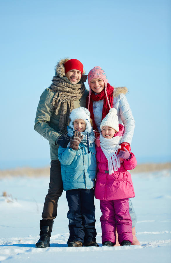 Family in winterwear. Happy family of four in winterwear looking at camera outdoors royalty free stock photography