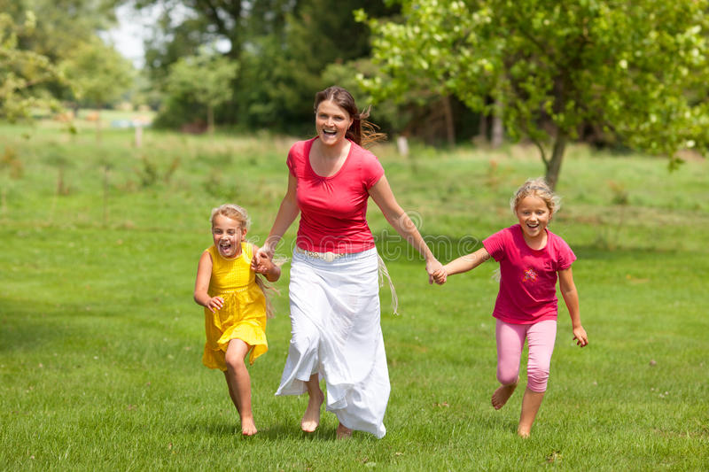 Family woman and girls running outdoor smiling stock photos