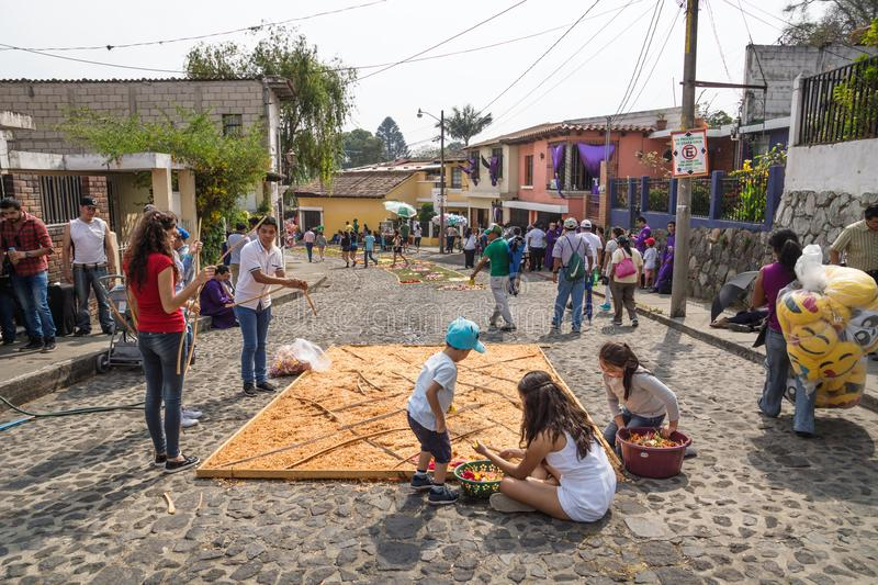 Family working on alfombres, carpets made by coloured sawdust on the cobbled streets for the procession San Bartolome de stock photo