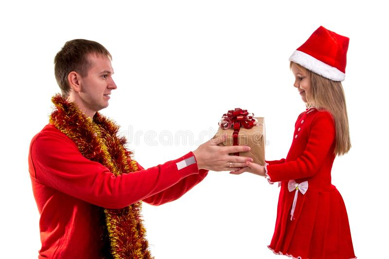 Family xmas time. Father gives a gift to daugter. Profile image. Daughter and father wearing santa hats and tinsel. Around the neck. Landscape image royalty free stock photo
